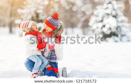 happy family mother and child daughter on a winter walk outdoors drinking tea