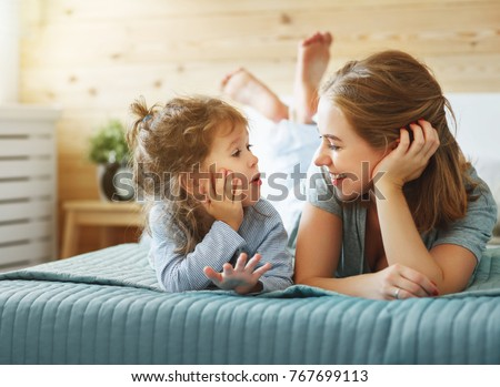 Happy family mother and child daughter play and laughing in bed #767699113