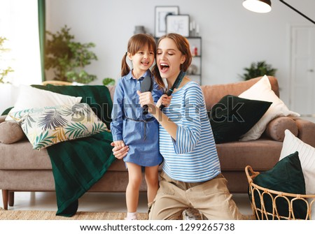 happy family mother and child daughter play at home and sing with combs