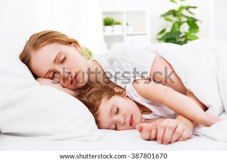 happy family mother and child daughter sleeping in bed embracing #387801670