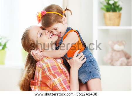 happy family mother and child girl daughter playing  laughing and hugging at home