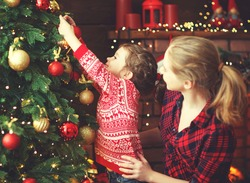 happy family mother and child girl decorated a Christmas tree