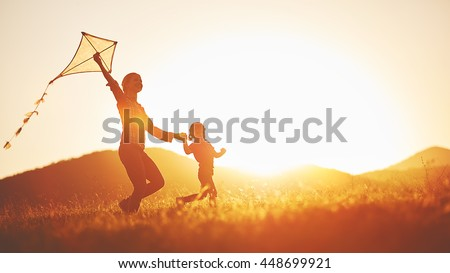 happy family mother and child run on meadow with a kite in the summer on the nature #448699921
