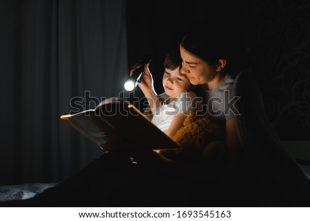 happy family mother and child son reading a book with a flashlight. Family before going to bed mother reads to her child son book near a flashlight in the evening. Foto stock ©