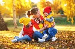 happy family mother and children on   autumn walk in   park
