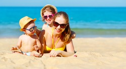 Happy family mother and children play and laugh at summer on the beach