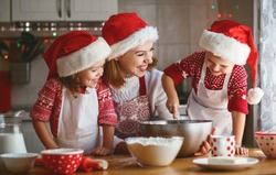 happy family mother and children son and daughter bake cookies for Christmas