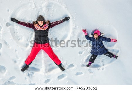 Happy family, mother and cute daughter making snow angel while lying on snow.  #745203862