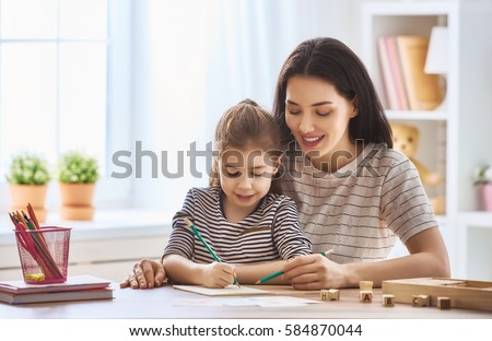 Happy family. Mother and daughter are learning to write. Adult woman teaches child the alphabet. #584870044
