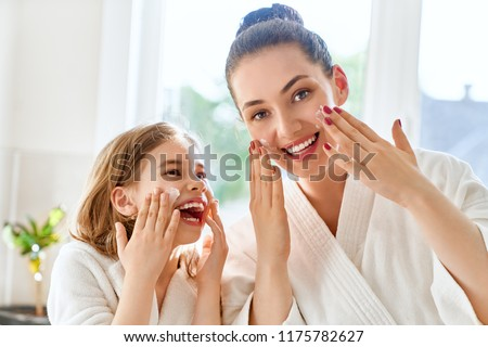Happy family! Mother and daughter child girl are caring for skin in the bathroom.