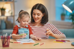Happy family. Mother and daughter drawing together. Adult woman helping to child girl.