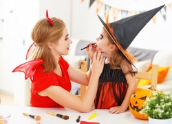 happy family mother and daughter getting ready for halloween make make-up