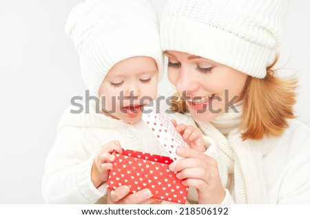 happy family mother and daughter in white hats with Christmas present in winter