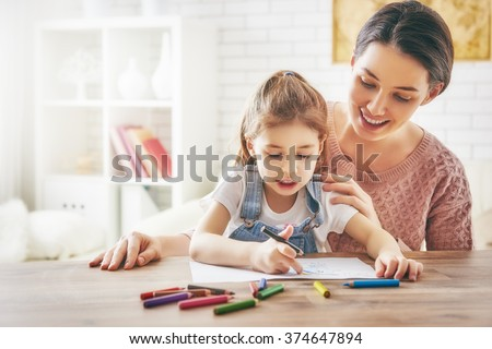 Happy family. Mother and daughter together paint. Adult woman helps the child girl. #374647894