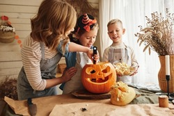Happy family mother and kids carving pumpkin for Halloween holiday together, preparing for holiday party in kitchen, mom with little daughter and son smiling having fun while creating Jack-o-lantern
