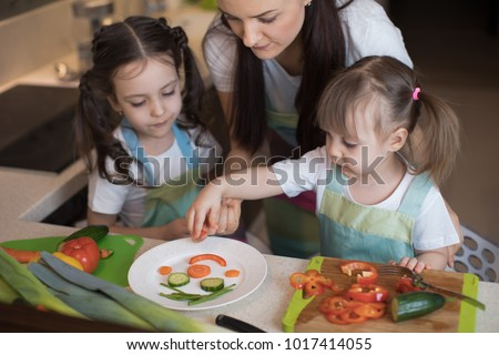 happy family mother and kids daughter are preparing healthy food, they improvise together in the kitchen