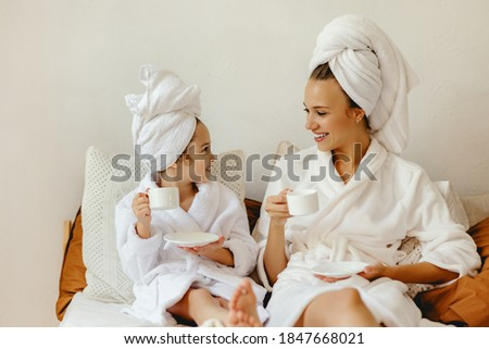 happy family mother and little daughter in bathrobe and towels est and relax with a Cup of coffee in bed at home