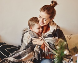 happy family mother and loving son hug and laugh wrapped in a warm blanket on a cozy winter evening at home