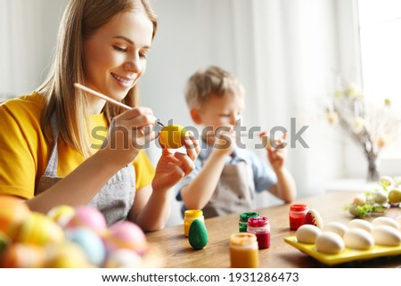 Happy family: mother and son sitting at table at home and painting eggs with gouache while preparing for Easter holiday