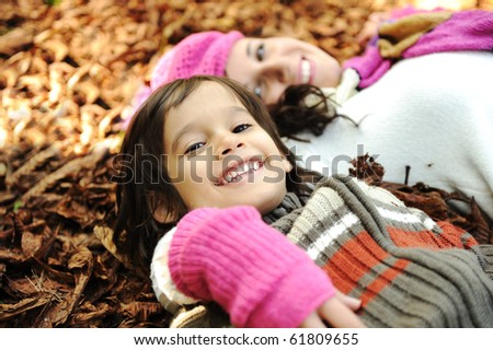 Happy family, mother and son, woman and child on autumn orange leaves. Outdoor.