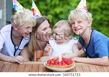 Happy family, mother and three children having fun celebrating first birthday of one year old baby girl