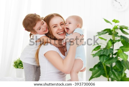 happy family mother and two children, son and daughter in bed playing Stockfoto ©