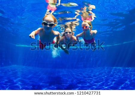Happy family - mother, baby son, daughter in goggles swim, dive in pool with fun - jump deep down underwater. Healthy lifestyle, people water sport activity, swimming lessons on holidays with kids