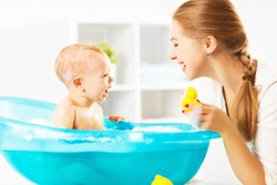 Happy family mother bathes the baby in a blue bath
