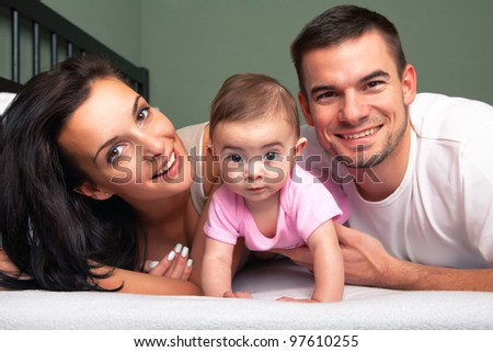 Happy family - mother, father and baby on the bed