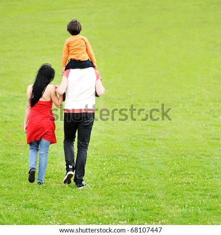 Happy family; mother, father and child, walking together in nature on green meadow, piggyback