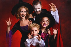 happy family mother father and children in costumes and makeup on a celebration of Halloween on dark red background