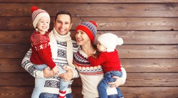 happy family mother, father and children  in winter hats on an empty wooden background