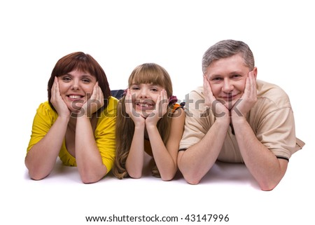 Happy family. Mother, father and little daughter are smiling . Woman, man and girl are lying on the floor and posing happily on white background.