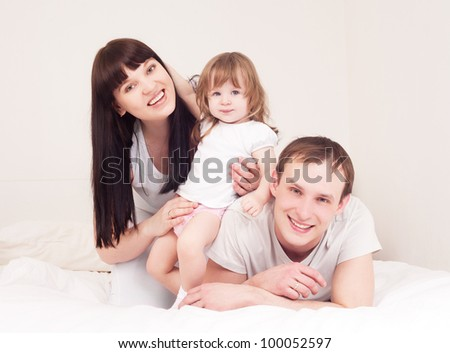 happy family; mother ,father and their baby in bed at home