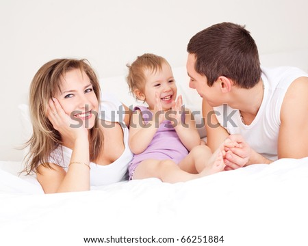 happy family, mother ,father and their baby on the bed at home (focus on the woman)