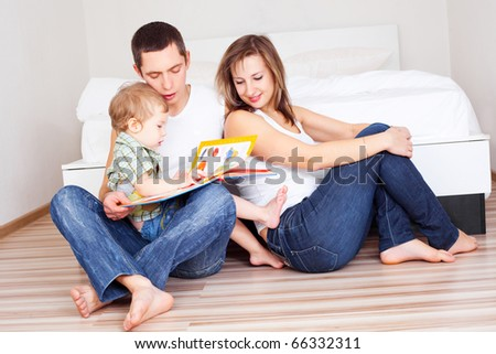 happy family, mother ,father and their baby read a book at home (focus on the father)
