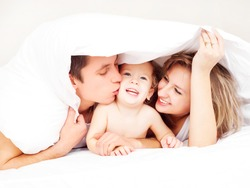 happy family, mother ,father and their baby under the blanket on the bed at home (focus on the man)
