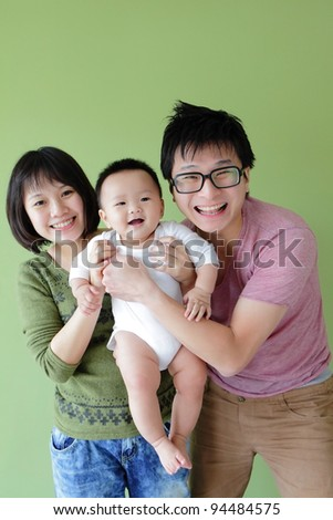 happy family, mother ,father and their baby with green background, model are asian family
