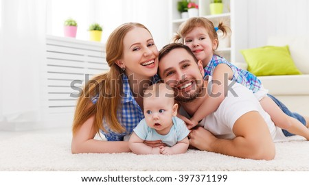 happy family mother, father and two children playing and cuddling at home on floor