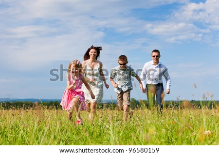 Happy family - mother, father, children - playing on a meadow in summer under blue sky