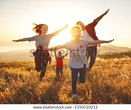 Happy family: mother, father, children son and  daughter on nature  on sunset