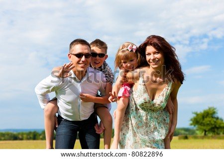 Happy family - mother, father, children - standing on a meadow in summer piggyback the kids