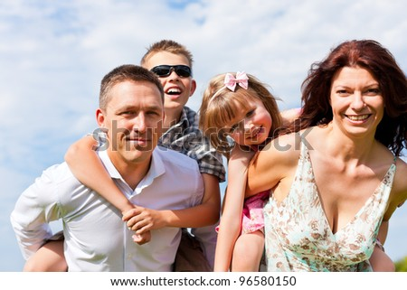 Happy family - mother, father, children - standing on a meadow in summer under blue sky