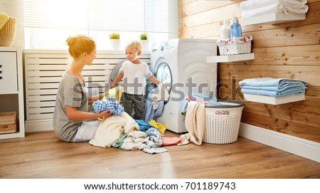 Happy family mother  housewife and children in the laundry load a washing machine #701189743