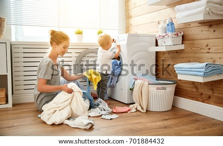 Happy family mother  housewife and children in the laundry load a washing machine #701884432