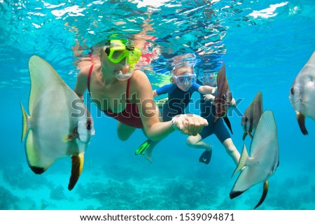 Happy family - mother, kids in snorkeling mask dive underwater, explore tropical fishes in coral reef sea pool. Travel active lifestyle, beach adventure, swimming activity on summer holiday with child