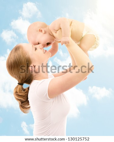 happy family. Mother throws up and kissing baby in the sky in nature