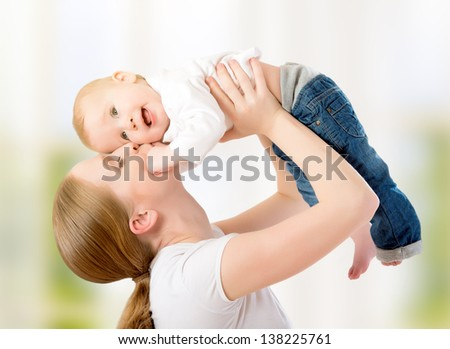 happy family. Mother throws up  baby, playing at home