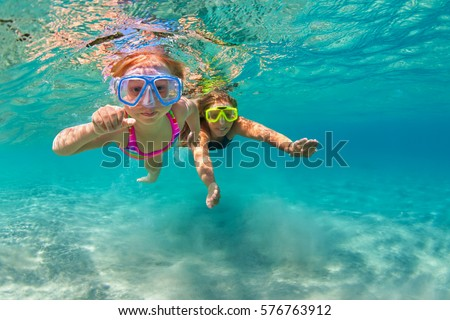 Happy family - mother with baby girl dive underwater with fun in sea pool. Healthy lifestyle, active parent, people water sport outdoor adventure, swimming lessons on beach summer holidays with child. #576763912