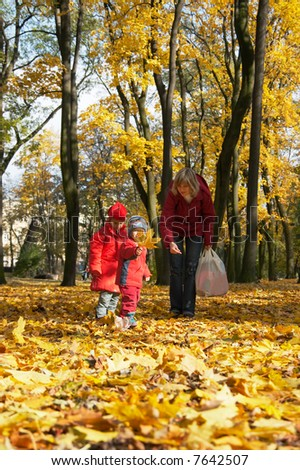 Happy family (mother with small boy and girl) in golden autumn city park
